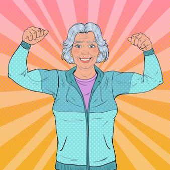 Pop art lächelnde ältere reife frau, die muskeln zeigt. gesunder lebensstil. glückliche starke großmutter.