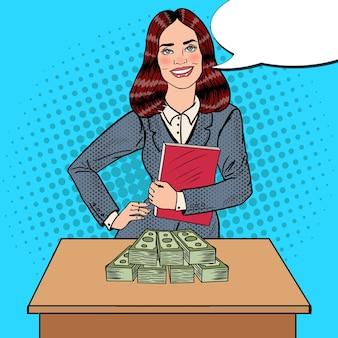 Pop art lächelnde geschäftsfrau, die mit geld hinter dem tisch steht.