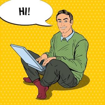 Pop art lächelnder junger mann, der mit laptop arbeitet. illustration
