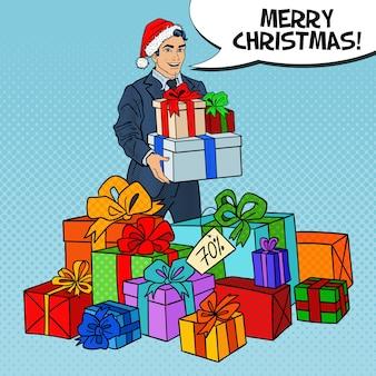 Pop-art-mann in der weihnachtsmütze mit geschenken auf weihnachtsverkauf.
