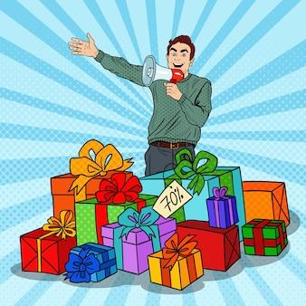 Pop-art-mann mit megaphon, das großen verkauf fördert, der in geschenkboxen steht.
