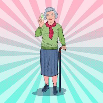 Pop art senior frau hält medizinpillen