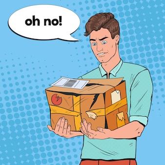 Pop art unglücklicher mann, der beschädigtes paket hält. unprofessioneller lieferservice. kerl mit geknacktem paket.