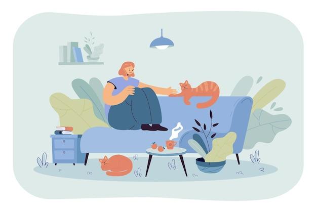 Positive dame, die auf gemütlichem sofa mit katzen sitzt. karikaturillustration