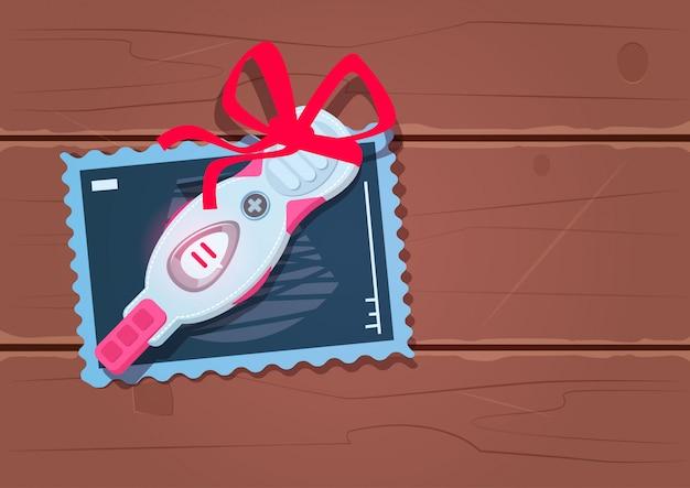 Positiver schwangerschaftstest mit rotem band-bogen auf hölzernem beschaffenheits-hintergrund