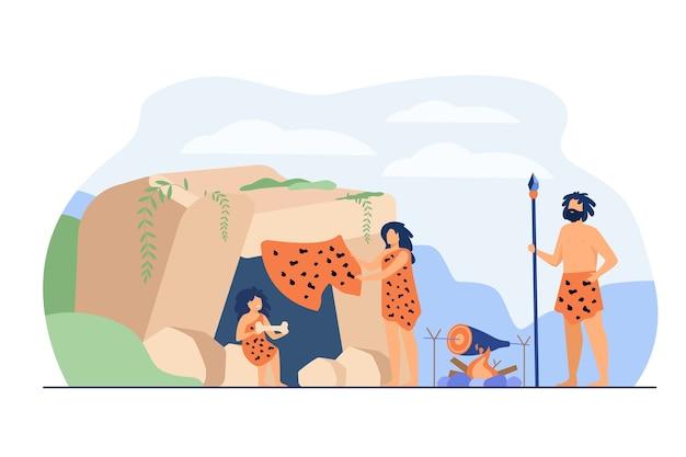 Prähistorisches familienpaar und kind, das leopardenfelle trägt und essen am höhleneingang kocht. vektorillustration für steinzeitalter der alten leute, höhlenmensch-abendessenkonzept