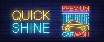 Premium Autowasch Leuchtreklame. Automobil unter Dusche und helle Aufschrift auf Backsteinmauer.