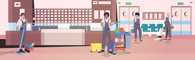 Professionelle reinigungskräfte mischen hausmeister mit reinigungsgeräten und arbeiten horizontal im inneren des krankenhauskorridors zusammen