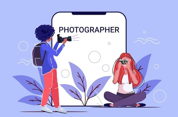 Professionelle weibliche fotografen, die foto-foto-mix-race-girls machen, die mit digitaler dslr-kamera smartphone-bildschirm online-mobile-app in voller länge schießen