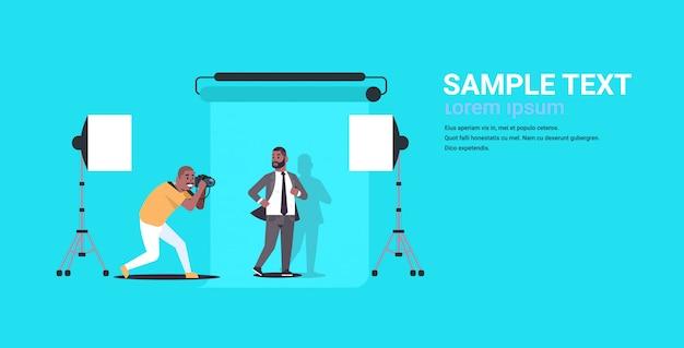 Professioneller fotograf, der geschäftsmann des kameraschießens im formellen verschleißmodell verwendet, das im horizontalen kopierraum des modernen fotostudios horizontaler voller länge aufwirft