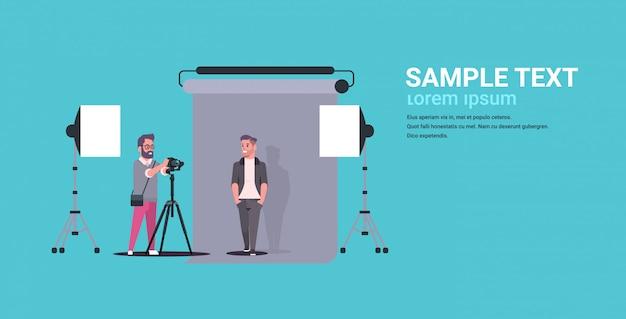 Professioneller fotograf, der geschäftsmann des kameraschießens im formellen verschleißmodell verwendet, das im modernen fotostudioinnenraum horizontalen flachen kopierraum der vollen länge aufwirft