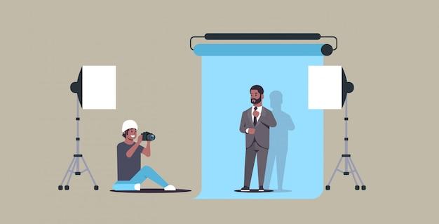 Professioneller fotograf, der geschäftsmann des kameraschießens im formellen verschleißmodell verwendet, das in der horizontalen vollen länge des modernen fotostudios posiert