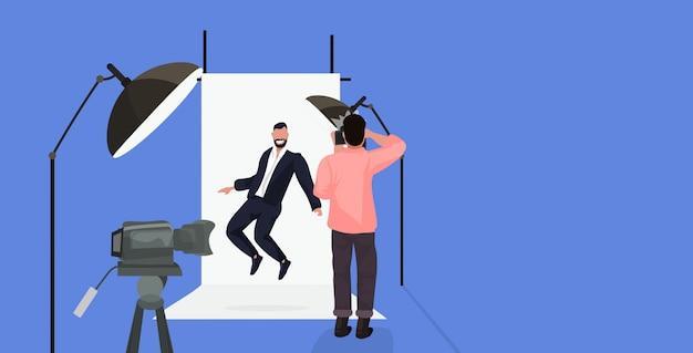 Professioneller fotograf, der kameramann verwendet, der geschäftsmann in der formellen kleidung aufwirft, die in der horizontalen vollen länge des modernen fotostudios aufwirft