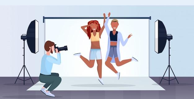 Professioneller fotograf, der kameramann verwendet, der schöne sexy frauenmodelle aufwirft, die modernes fotostudio interieur horizontal in voller länge posieren und springen