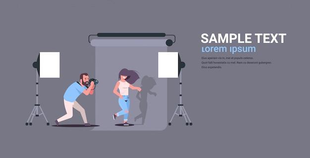 Professioneller fotograf, der kameramann verwendet, der schönes sexy frauenmodell schießt, das im modernen fotostudio-innenraum horizontale wohnung in voller länge aufwirft