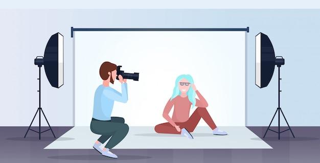 Professioneller fotograf mit kameramann, der schönes sexy frauenmodell schießt, das modernes fotostudio-innenraum horizontal in voller länge aufwirft