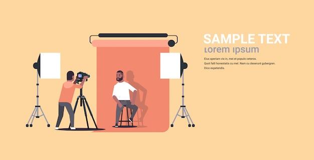 Professioneller fotograf unter verwendung des geschäftsmannes des kameraschießens in der formellen abnutzung, der auf stuhlmodell sitzt, das im horizontalen kopierraum des modernen fotostudios horizontaler voller länge aufwirft