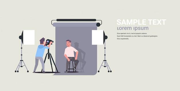 Professioneller fotograf unter verwendung des geschäftsmannmodells der kameraaufnahme, das im horizontalen flachen kopierraum des modernen fotostudio-innenraums in voller länge posiert