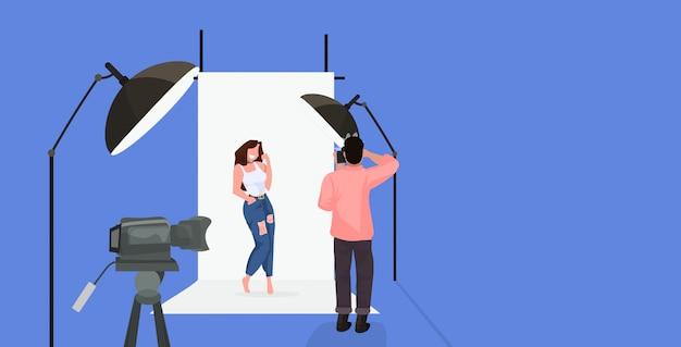 Professioneller fotograf unter verwendung des kameramannschießens schönes sexy frauenmodell, das im modernen fotostudio horizontale volle länge aufwirft