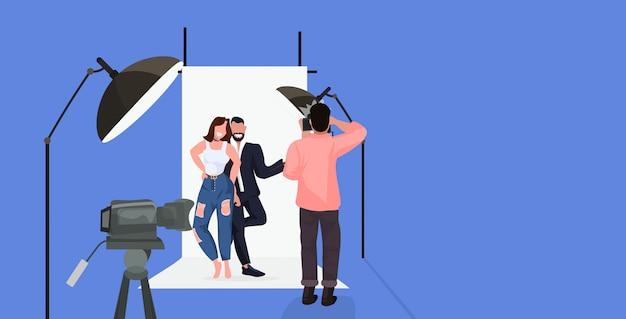 Professioneller fotograf unter verwendung eines kameramannschießpaares, das zusammen in der horizontalen vollen länge des modernen fotostudios posiert