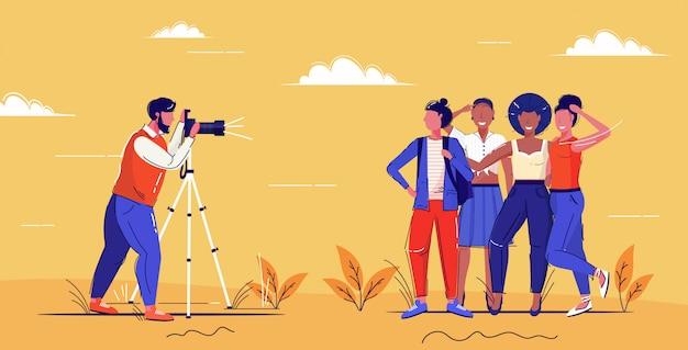 Professioneller männlicher fotograf mit digitaler dslr-kamera auf stativ-shooting-mix-race-girls, die zusammen für eine fotomode-shoot-konzept-skizze in voller länge posieren