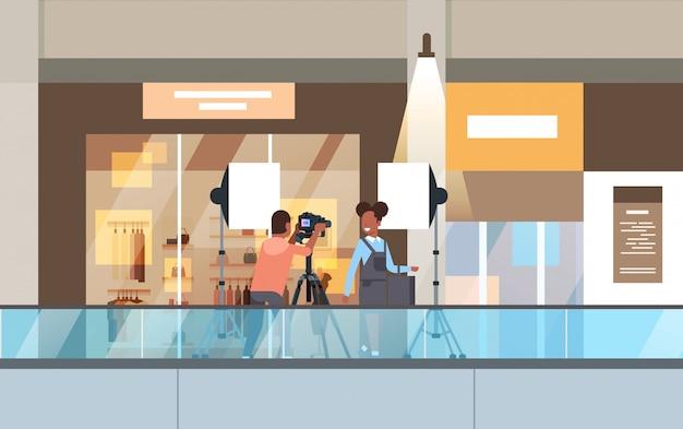 Professioneller mann fotograf mit dslr-kamera auf stativ schießen frau modell mädchen posiert in modernen einkaufszentrum einkaufszentrum supermarkt interieur horizontal in voller länge