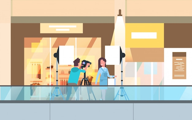 Professioneller mann fotograf mit dslr-kamera auf stativ schießen schöne frau modell mädchen posiert in modernen einkaufszentrum einkaufszentrum supermarkt interieur horizontal in voller länge