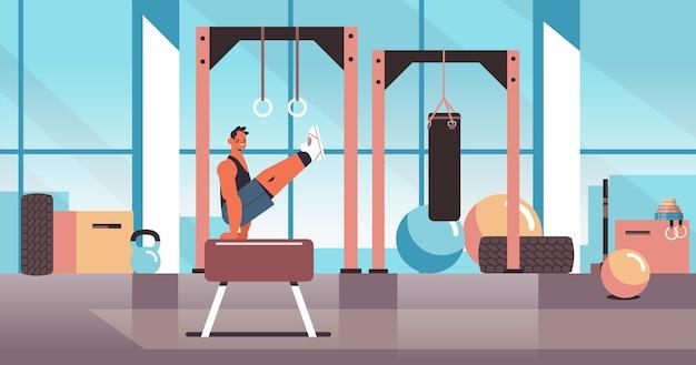 Professioneller turner, der körperliche übungen auf pauschenpferd macht, das fitness-training des gesunden lebensstils des modernen fitness-studio-innenraums ausarbeitet