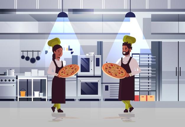 Professionelles kochpaar, das tabletts mit frischer pizza afroamerikaner-mannfrau in uniform hält, die zusammen kochendes lebensmittelkonzept modernes restaurantkücheninnenraum stehen