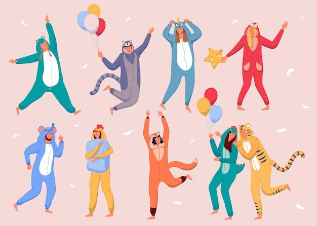 Pyjama-heimparty. glückliche leute, die tierkostüm-onesies tragen und feiertag feiern. junge männer und frauen zeichentrickfiguren in kigurumi, die spaß zu hause pyjama-partyballons und fliegende federn haben