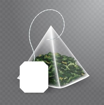 Pyramidenförmiger teebeutel mit grünem tee im inneren. realistische illustration des teebeutels mit leerem weißem etikett auf transparentem hintergrund.