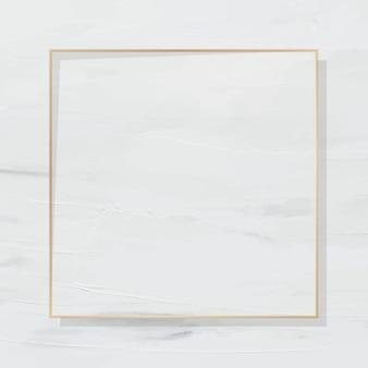 Quadratischer goldrahmen auf weiß lackiertem hintergrund