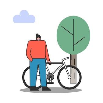 Radfahrerin mit fahrrad im park. weibliches stehen mit fahrrad, das ruhe während der morgenfahrt hat