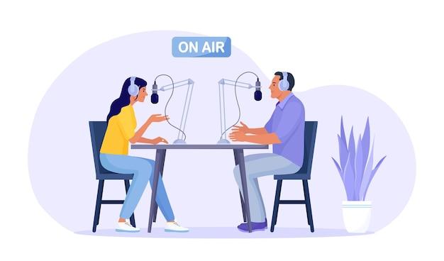Radiomoderator interviewt gäste im radiosender. mann und frau in kopfhörern, die mit mikrofonen sprechen, die podcasts im studio aufnehmen. massenmedienübertragung