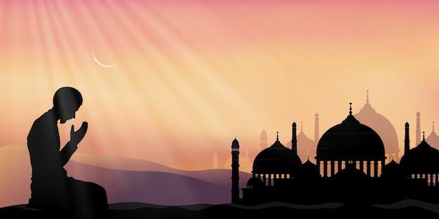 Ramadan kareem mit gebet und moschee, silhouette muslimischer mann, der ein flehen (salah) macht, das auf wüste sitzt, arabische person in traditioneller kleidung, die im freien betet, islamische moschee mit halbmond und stern