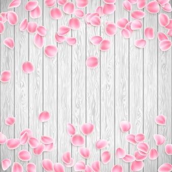 Realistische blütenblätter auf einem weißen hölzernen hintergrund.