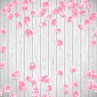 Realistische sakura-blütenblätter auf einem weißen hölzernen hintergrund.