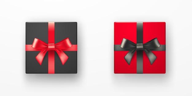 Realistische schwarze und rote geschenkboxen mit bändern über weißem hintergrund. weihnachtsillustration