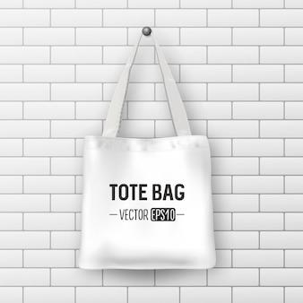 Realistische vektorweiße textil-einkaufstasche. nahaufnahme auf backsteinmauerhintergrund. designvorlage für branding, mockup. eps10-abbildung.