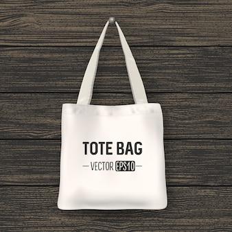 Realistische vektorweiße textil-einkaufstasche. nahaufnahme auf hölzernem hintergrund. designvorlage für branding, mockup. eps10-abbildung.