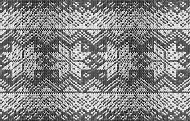 Realistischer gestrickter hintergrund mit schneeflocken. vektor nahtlose textur aus wolle grau stricken. norwegisches muster. vorlage von strickwaren für tapeten, weihnachts- und neujahrsgrußkarten, webseitenhintergrund.