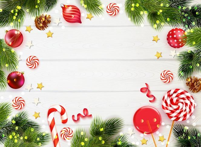 Realistischer holztischhintergrund gerahmt mit tannenbaumzweigbonbons und weihnachtsdekorationen