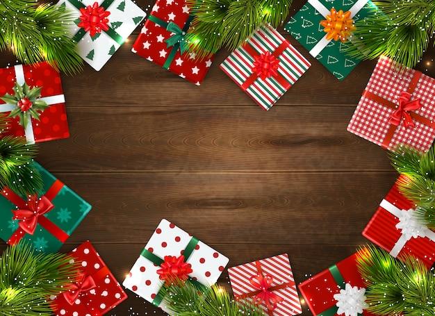 Realistischer weihnachtshintergrund mit bunten geschenkboxen und tannenzweigen auf holztisch