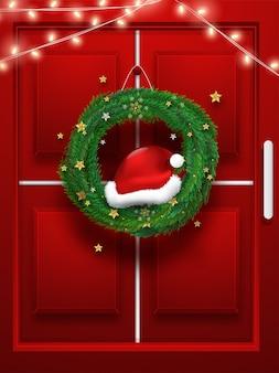 Realistischer weihnachtskranz mit der belichteten beleuchtungs-girlande, die an der roten tür hängt.
