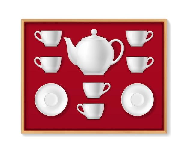 Realistisches teeservice aus keramik, teetassen, kanne, tassen und porzellan. vektor 3d weiß gefärbte geschirr teekanne, tassen und untertassen zum trinken von heißen getränken in holzkiste mit rotem samt ummantelung von oben liegend