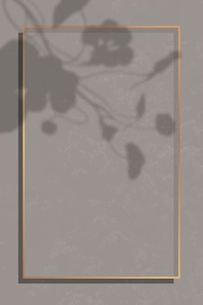Rechteckiger goldrahmen auf blattbeschattetem braunem marmorhintergrund