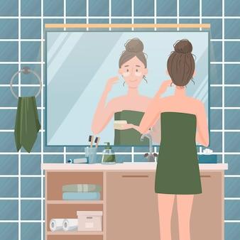Regelmäßige hautpflege. karikatur junge frau, die sich der haut im badezimmer kümmert.