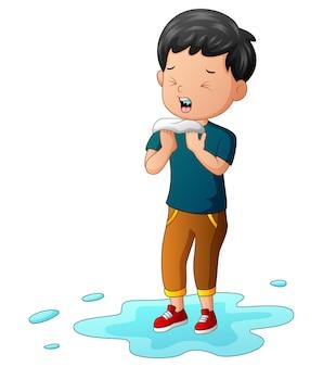 Regenzeit, ein junge hat sich grippe und niesen eingefangen
