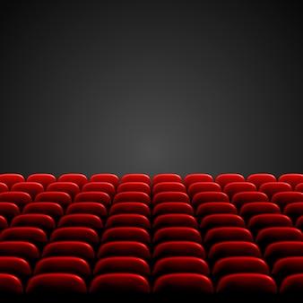 Reihen roter kino- oder theatersitze vor einem schwarzen leeren bildschirm. breites leeres kino-auditorium mit roten sitzen.