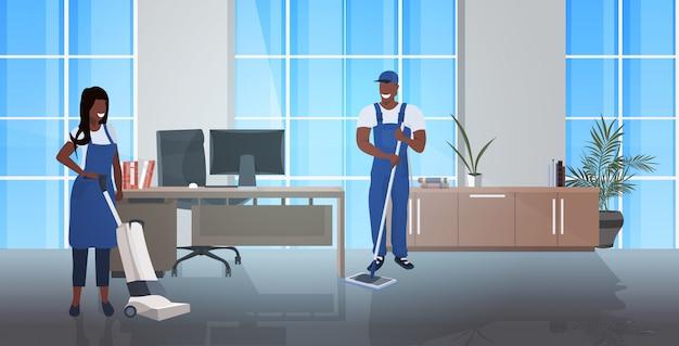 Reinigungspaar mit mopp und staubsauger afroamerikaner hausmeister team in uniform zusammenarbeiten reinigungsservice konzept modernes büro interieur horizontal in voller länge